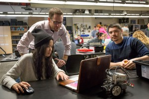 Assistant Professor Adam Carberry stands behind two students working on a project in class