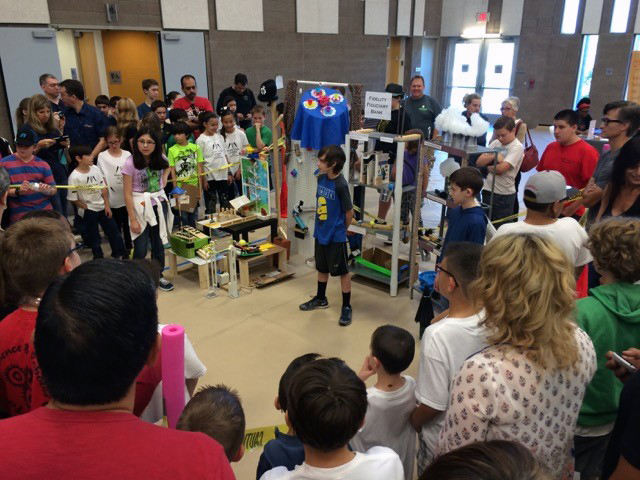 Team members of the RubeCrafters Division I team from Veritas Homeschoolers present their machines to parents and judges. The RubeCrafters placed 2nd place in Division I and also won the STEAM award for Art.