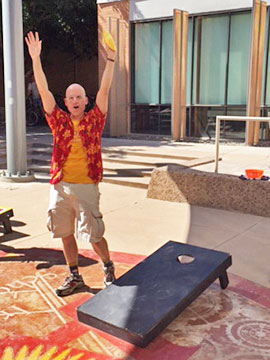 Jonathan Klane, assistant director of Safety Programs for the Ira A. Fulton Schools of Engineering, celebrates a great shot during the first round of the Cornhole Tournament to raise funds for United Way. Photographer: Rick Martorano/ASU.