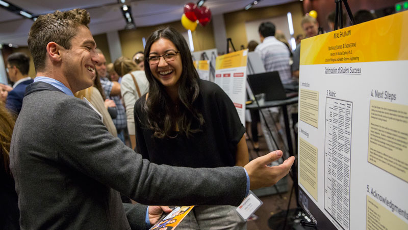 Two students discuss research at the Fulton Undergraduate Research Initiative Symposium