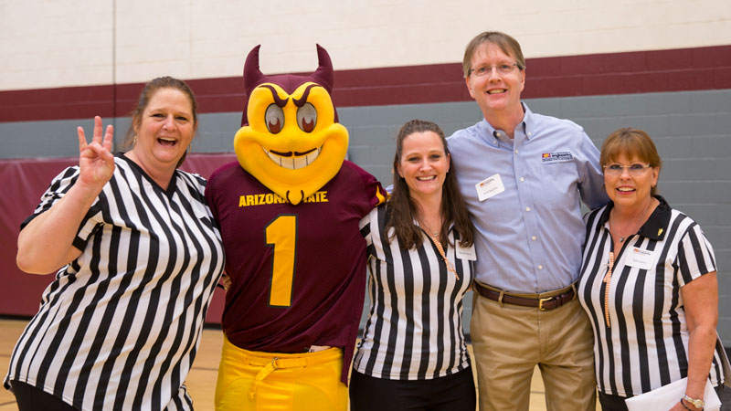 Sparky, Dean Kyle Squires and volunteers pose at the Service and IMPACT Awards Breakfast