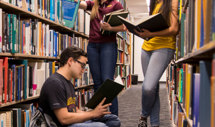 Photo of students reading books at the library.