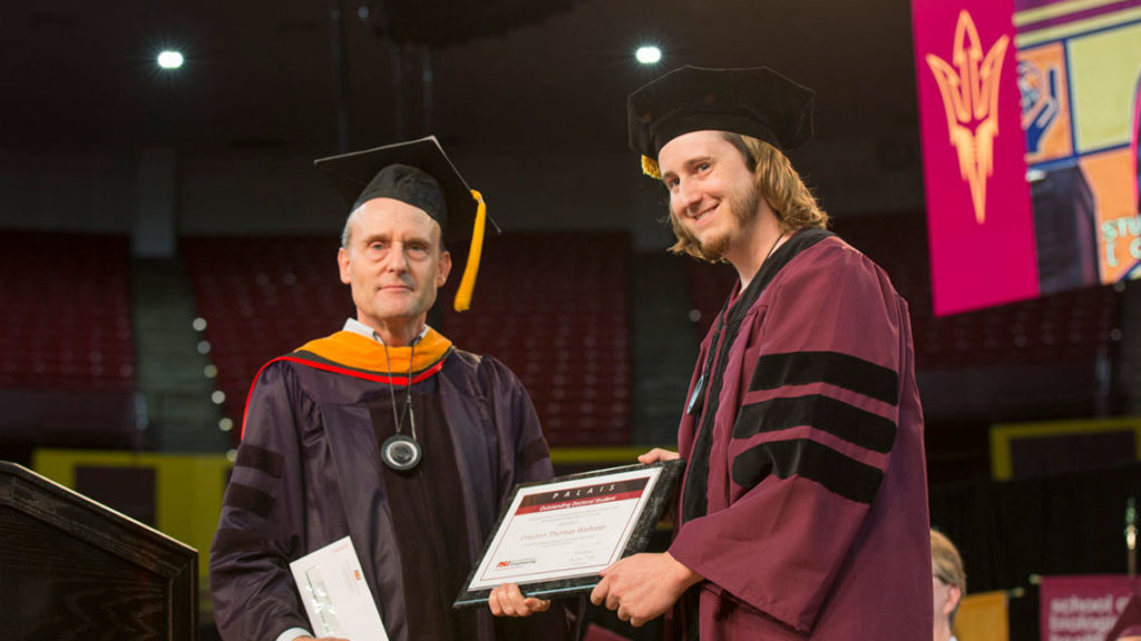 Professor Steve Phillips, director of the School of Electrical, Computer and Energy Engineering, presents recent doctoral graduate Preston Webster with the Palais Outstanding Doctoral Student Award at the Ira A. Fulton Schools of Engineering Spring 2016 Maroon Convocation Ceremony at Wells Fargo Arena, May 10, 2017. Photographer: Jessica Hochreiter/ASU