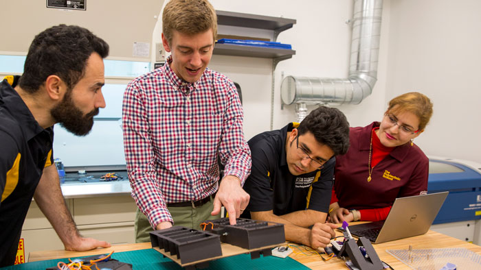 Daniel Aukes (second from left) and his students look at robots in his lab.