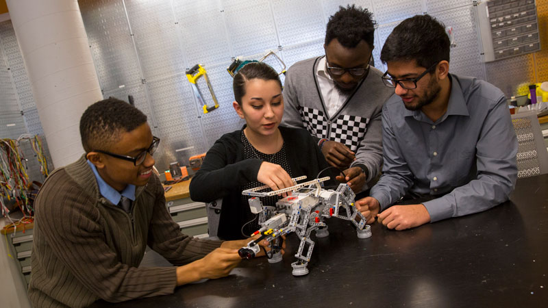Four students work on a robotics project