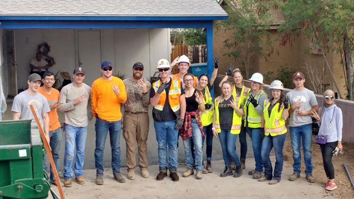 Students in construction gear pose for a photo.