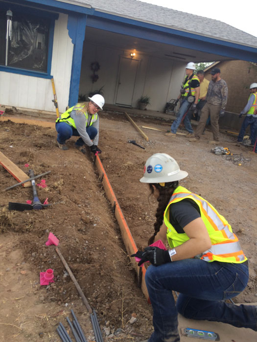 Students prepare an area for a concrete slab.
