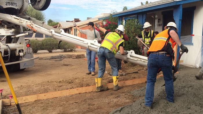 Students pour concrete.