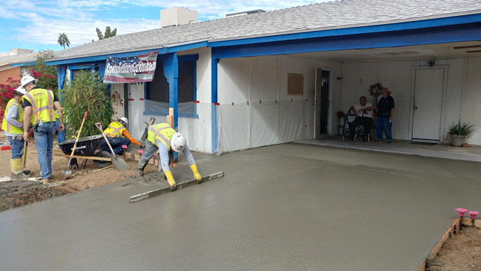 Students smooth out the wet concrete.