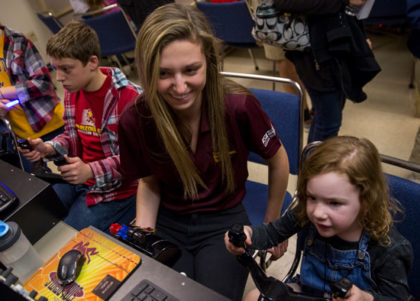 A Fulton Schools student works with visiting children on an avionics activity.