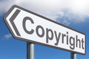 """A photo of a road sign that says """"copyright"""" with an arrow pointing to the left"""