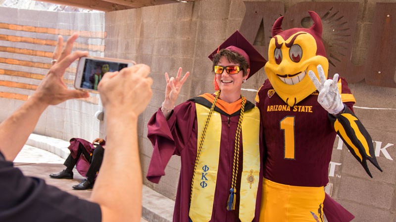 Sparky poses with a grad at Convocation.
