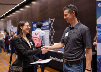 A student and recruiter shake hands at Career Fair.