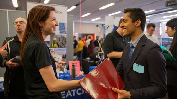 A recruiter and student shake hands at Career Fair