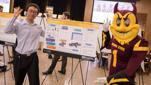Sparky and a student pose at the FURI Symposium.