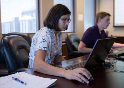 Two students work on laptops