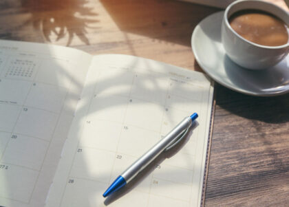 A planner, pen and coffee on a desk.